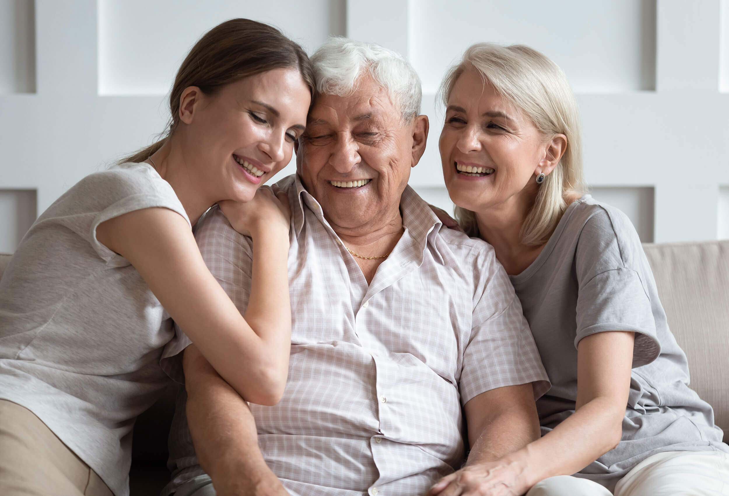 Two women and an elderly man smiling